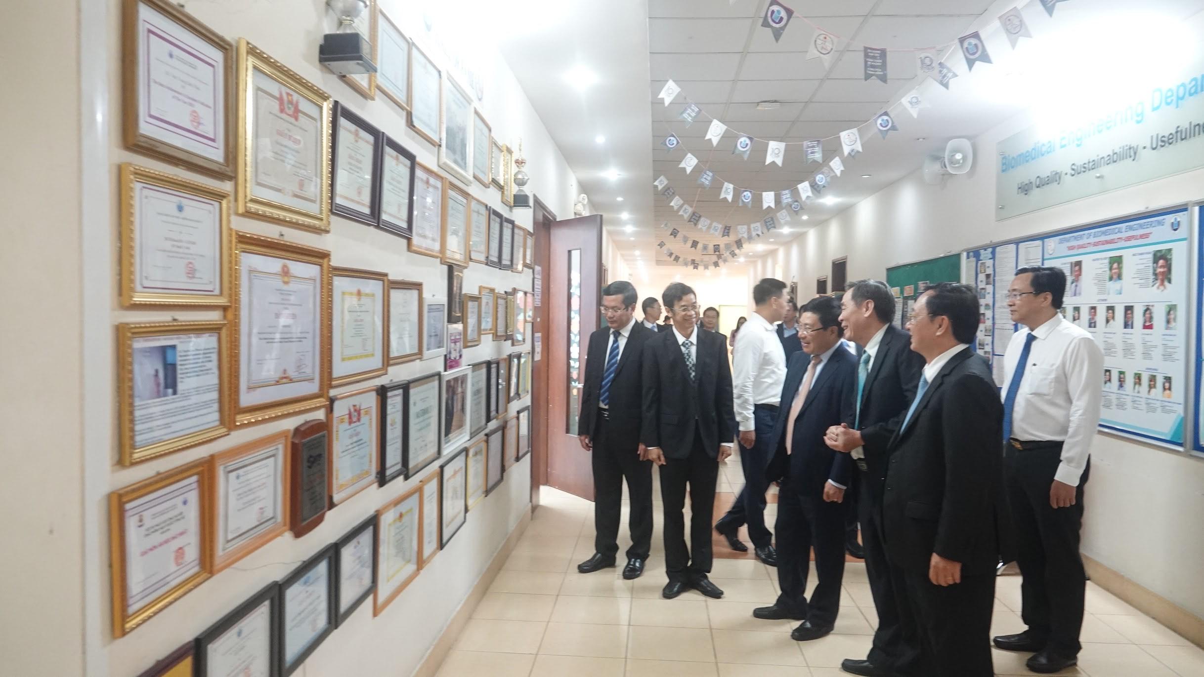Phó Thủ tướng Phạm Bình Minh và đoàn đại biểu trước Bức Tường Thành tích (Hall of Fame) treo những bằng khen mà giảng viên, sinh viên và cán bộ của Khoa KTYS đã nhận được